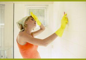 Женщина моет плитку в ванной