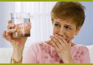 Женщина держит протезы в стакане
